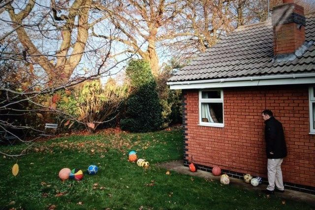 Young man in garden with footballs