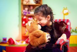 Young girl in a wheelchair with a teddy bear