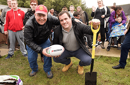 Two men holding a rugby ball in an allotment