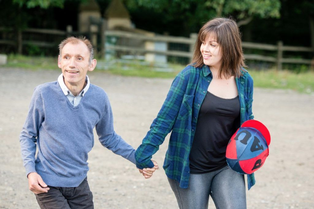 A woman holds the hand of a man with learning disabilities