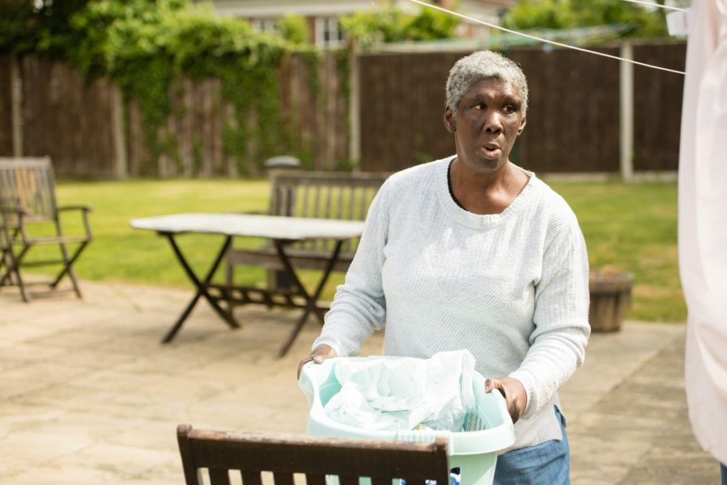 Woman in white top holding a laundry basket