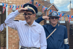 Two men dressed in World War Two uniforms, saluting